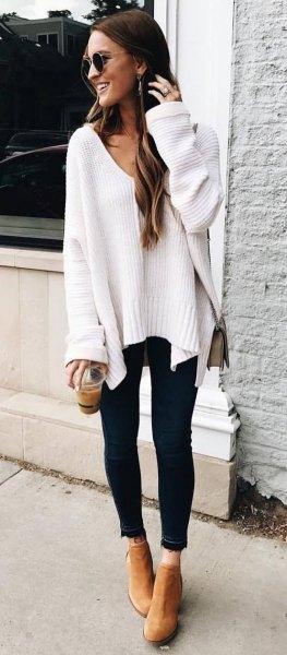 vit, tjock hösttröja med V-ringning och skinniga jeans med svart snitt