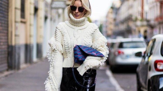 vit collegetröja med kabelmönster och svarta läderbyxor