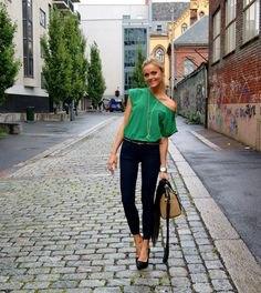 Ljus smaragdgrön topp med en axel och svarta skinny jeans