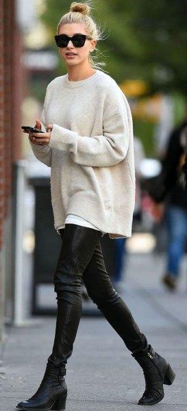 vit, tjock tröja med rund halsringning och svarta läderbyxor