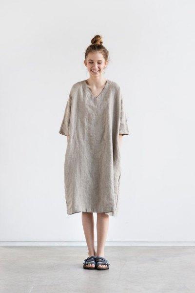 Bär en grå linne topp med V-ringning och halva ärmar som klänning