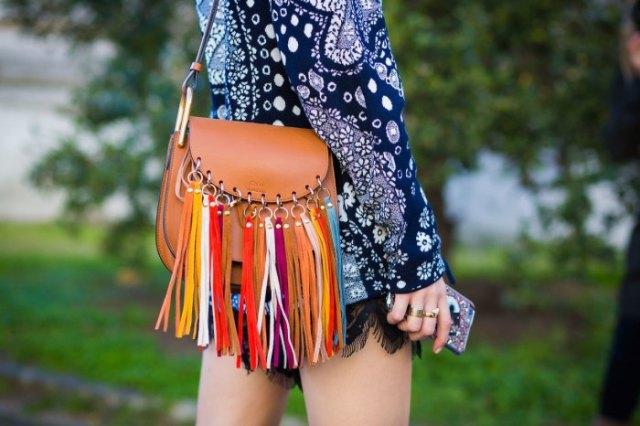 Mörkblå, långärmad tribal miniklänning med tribal-tryck och plånbok i brunt läder med fransar