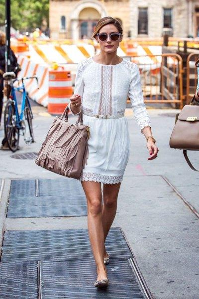 vit långärmad miniklänning med volang i midjan och ljusrosa läderplånbok med fransar