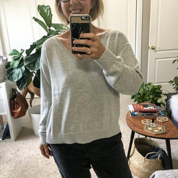grå V-ringad bomullströja och svarta jeans med raka ben