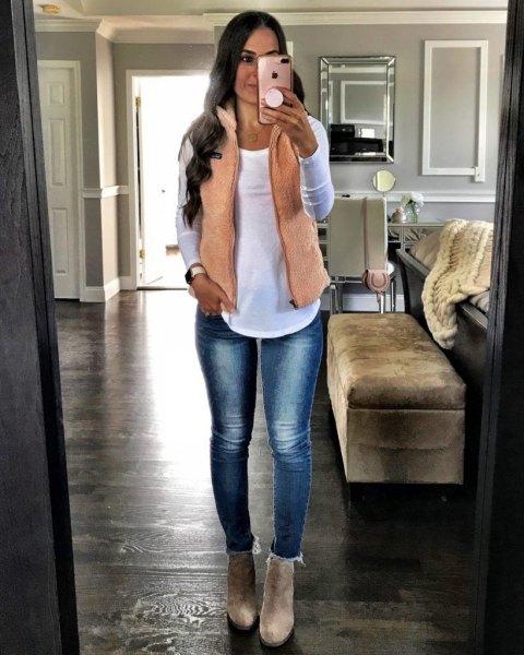 rodnande rosa väst med vit långärmad T-shirt och smala fleecefodrade jeans