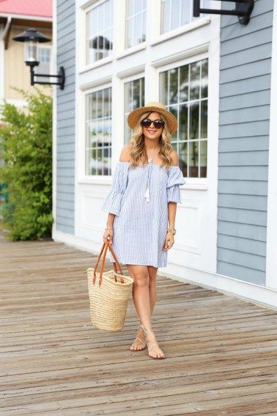 Blå och vit randig axelbandslös miniklänning med en halm shoppingväska