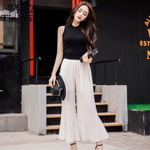svart ärmlös stickad tröja vita byxor