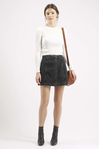 vit, kramad, ribbad tröja med svart minikjol i denim med knäppning