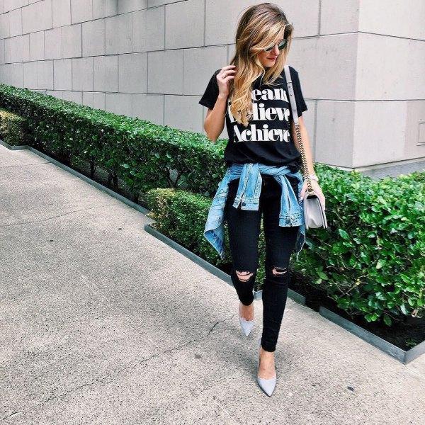svart tryckt t-shirt med rippade jeans och jeansjacka knuten runt midjan