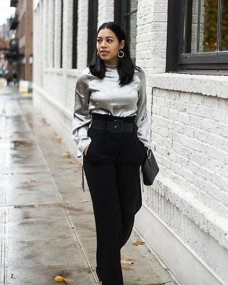 silverblus i metall med svarta byxor med hög midja och vida ben