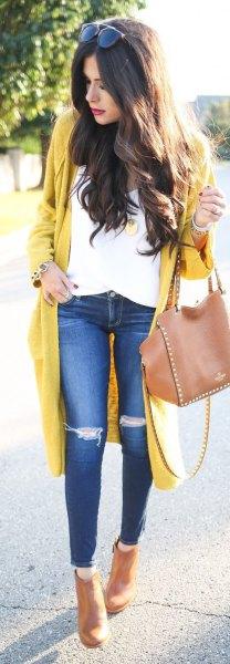 gul långdragen koftetröja med vit blus och rippade knäjeans