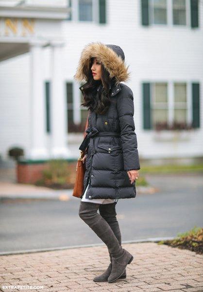 svart långlinnad pälsjacka med huva och vit tunikaklänning