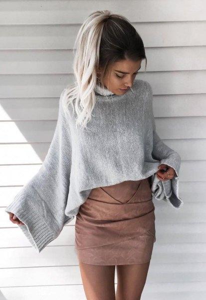 grå stickad tröja med vida ärmar och matchande matt läder kjol