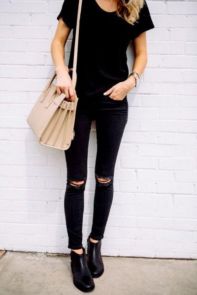 svart slim fit t-shirt med matchande smala jeans med en tår i knäet