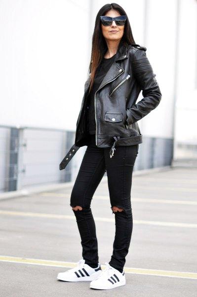 svart skinnbikerjacka med knästrimmade jeans i smal passform