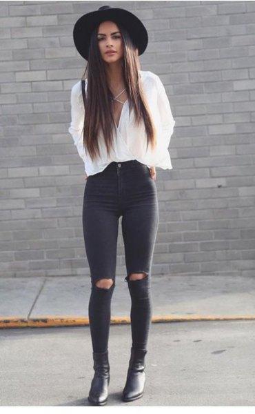 vit blus med V-ringning och svarta skinny jeans med tår i knäet