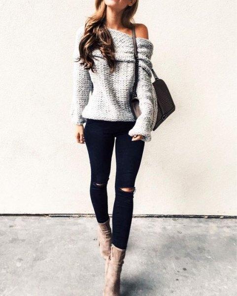 grå tröja utan axel med svarta, rippade jeans