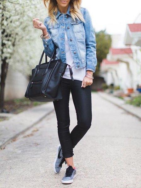 blå jeansjacka med svarta läderbyxor och grå vandringstennisskor