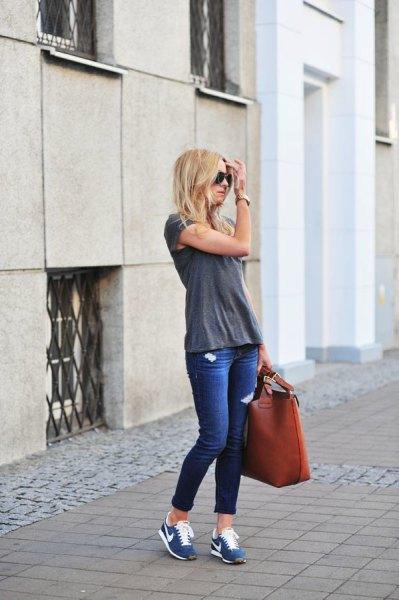 grå t-shirt med blå skinny jeans med manschetter och tennisskor