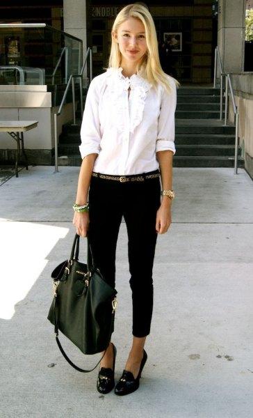 vit skjorta med volangknappar, svarta jeans med muddar och tofflor med tofsar