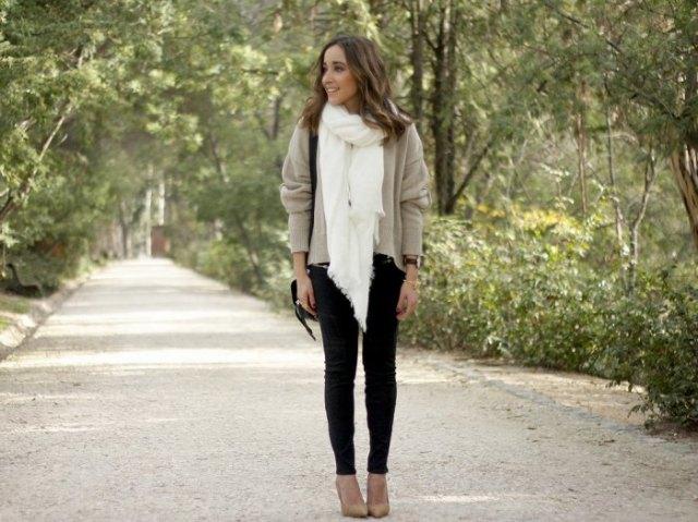 ljusgrå tröja med vit halsduk och svarta skinny jeans