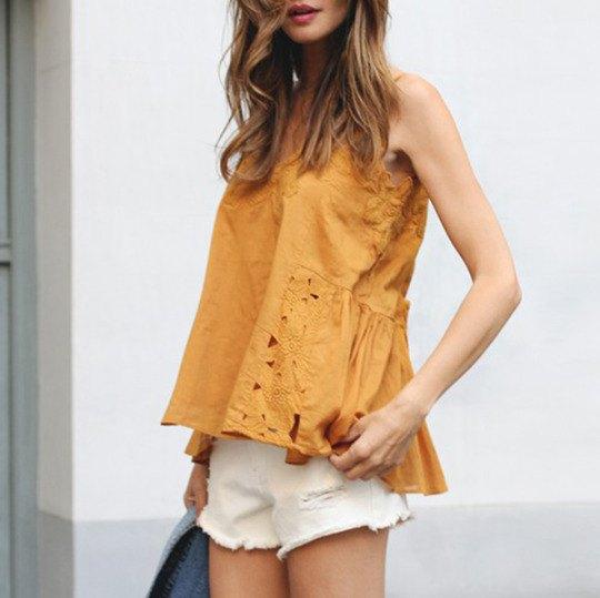 Ärmlös blus i guldspets med vita mini-shorts