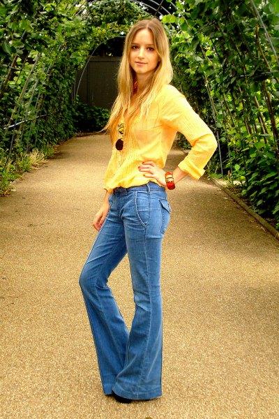 ljusgul långärmad blus med blå flared jeans