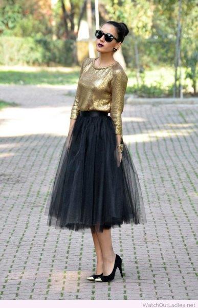 gyllene blus med svart midityllkjol