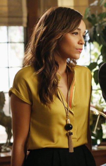 gyllene kortärmad sidenblus med knappar och svart kjol