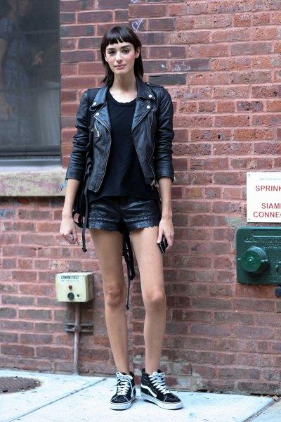 svart konstläderjacka med mini-jeansshorts och canvas-sneakers