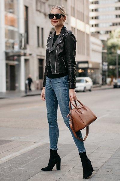 svart lädermotojacka med gråblå skinny jeans och stövlar med klackar