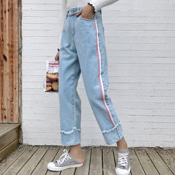 vit tröja med ljusblå, veckade jeans och grå canvas sneakers