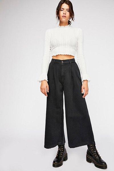 vit kortvarig tröja med mock-hals och svarta veckade jeans