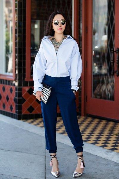 Ljusblå skjorta med knappar och mörka avsmalnande, veckade jeans