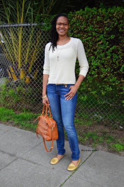 vit, passande tröja med blå skinny jeans och guld loafers med rundade tår