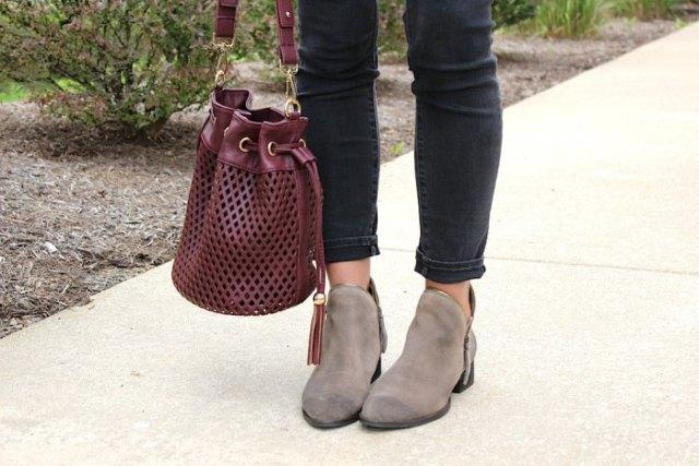 Bourgogne röd handväska i mjukt läder med en vit blus och svarta, smala snittade jeans