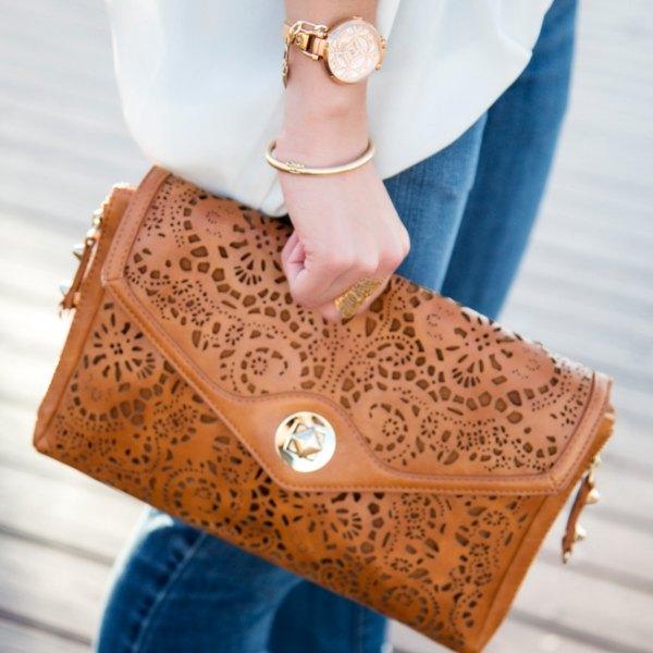 brun urringningskoppling i mjukt läder med vit chiffongblus och blå jeans