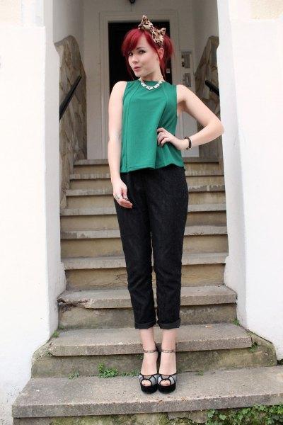 grön ärmlös topp med svarta byxor med muddar