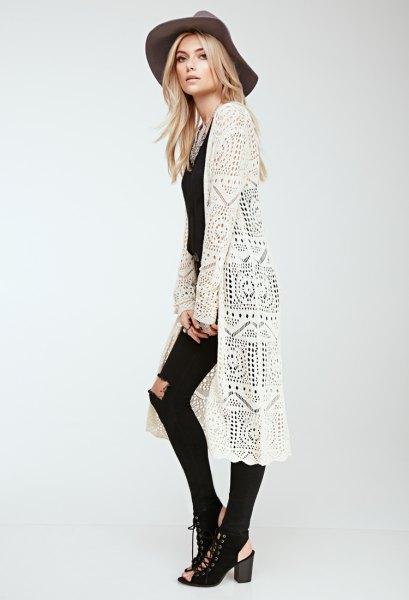 vit lång virkad vagga med svarta skinny jeans