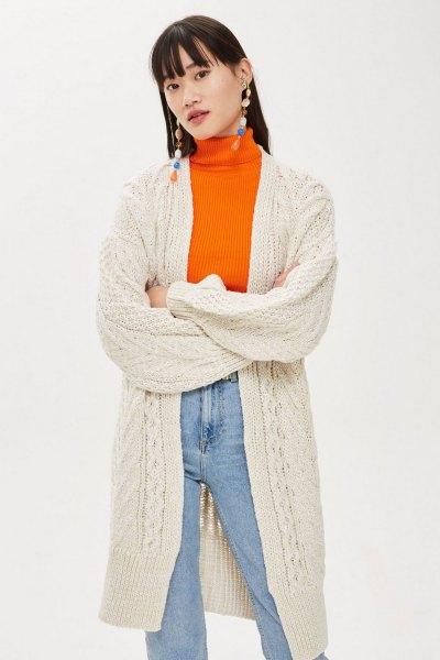 Krämfärgad långstickad kofta med orange tröja och mamma-jeans