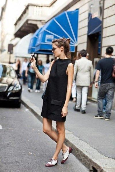 svart miniklänning med stand-up krage och vita och grå Oxford klädskor