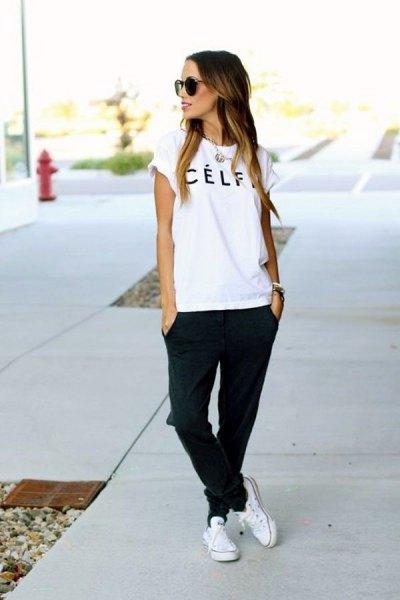 vit logotyp-t-shirt med svarta joggerjeans och sneakers