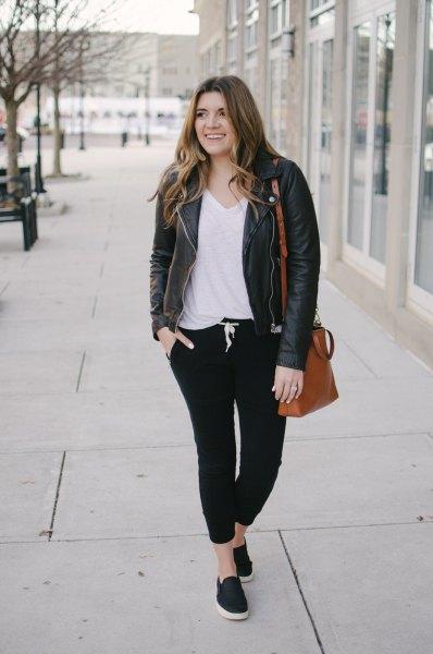 Läderjacka med vit V-ringad t-shirt och svarta joggerjeans