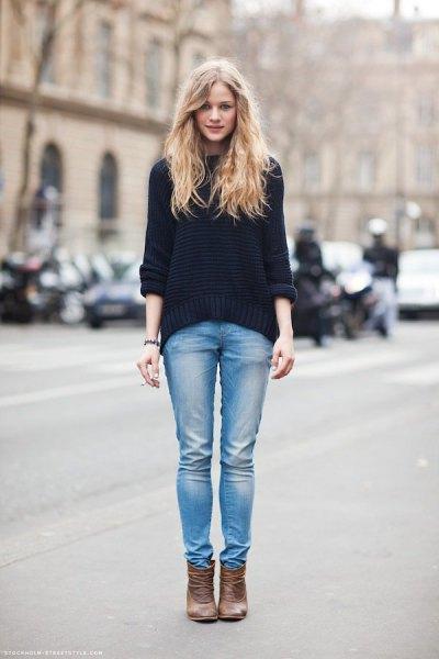 svart, tjock tröja med ljusblå jeans i smal passform och ljusbruna läderstövlar
