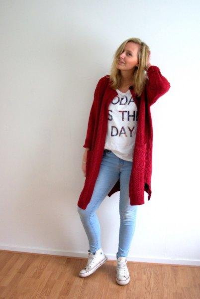röd lång kofta med vit tryckt t-shirt och ljusblå skinny jeans
