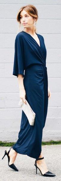 Mörkblå maxiklänning med halva ärmar och en vit koppling