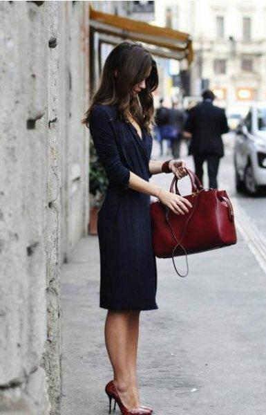 Mörkblå midiklänning med halva ärmar och en brun läderhandväska