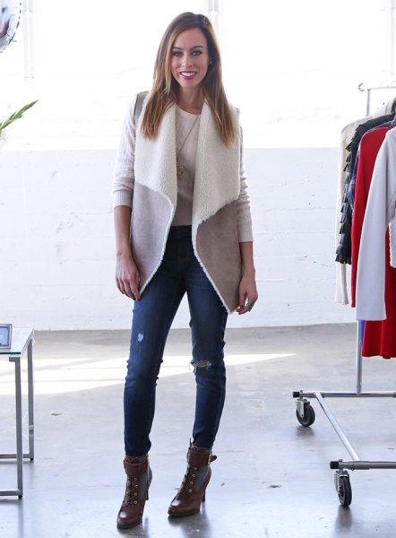 grå lammskinnsväst med trasiga smala jeans och stridsstövlar