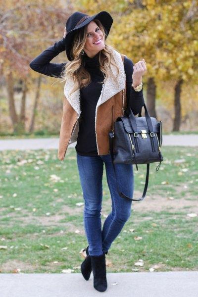 svart mock-neck tröja med kamel lammskinn väst och blå jeans