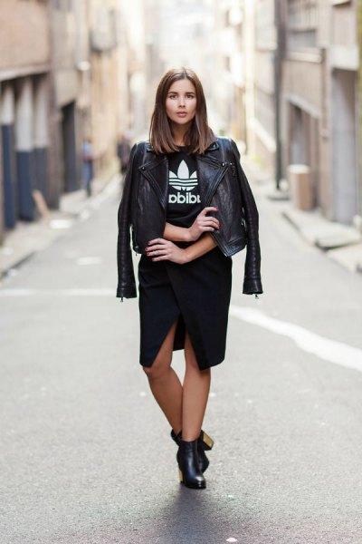 svart skinnjacka med grafisk t-shirt och knälång kjol